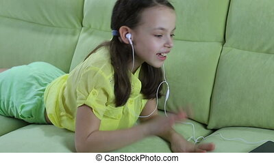Beautiful emotional girl listening to song on laptop and sings.