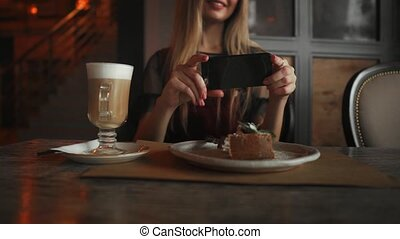 beautiful emotional happy girl is making photo of food in...