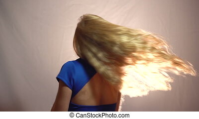 Beautiful Emotional Sexy Blonde Girl in Blue Dress Spinning Around in Studio with light Background.