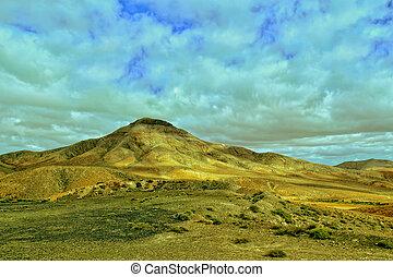 empty mysterious mountainous landscape from the center of the Canary Island Spanish Fuerteventura with a cloudy sky