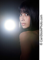 Beauty shot of Eurasian fashion model on black studio background