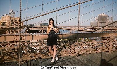 Beautiful European female blogger stands using smartphone...