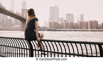 Beautiful European girl sitting on river embankment fence, looking back at camera smiling near Brooklyn Bridge, NYC 4K.