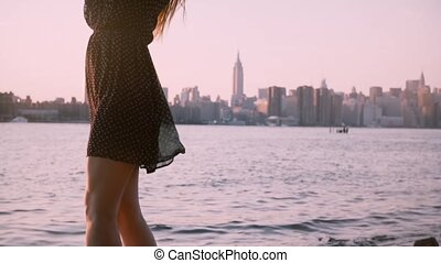 Beautiful European woman in black dress and sunglasses posing, smiling at camera on summer sunset, tilt up slow motion.