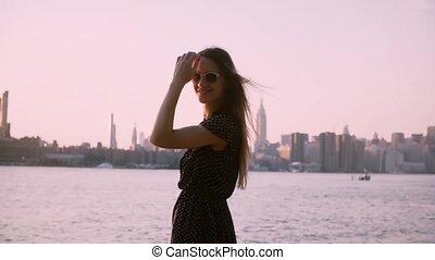 Beautiful European woman in sunglasses looks back at camera smiling, enjoying summer sunset, slow motion medium shot.