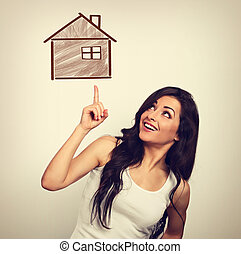 Beautiful excited casual woman pointing the finger up on small illustration wooden house. Insurance protection concept, investment to safety money. Vintage color style