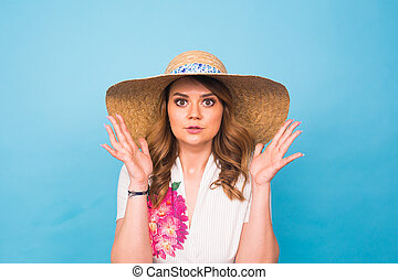 Beautiful excited surprised young woman over blue background with copy space.
