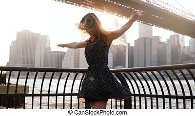 Beautiful excited traveler girl spinning on river embankment at Brooklyn Bridge with arms raised in the air slow motion.