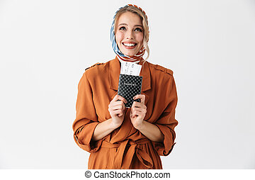 Beautiful excited young blonde pretty woman wearing silk scarf posing isolated over white wall background holding passport with tickets.