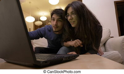 Beautiful excited young couple watching honeymoon exotic destination videos on laptop in the living room