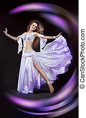 Beautiful exotic belly dancer woman in white suit oriental dance in motion isolated on black background. Colourful Studio Shot
