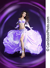 Beautiful exotic belly dancer woman in white suit oriental dance in motion isolated on black background. Colourful Studio Shot. Lights effect