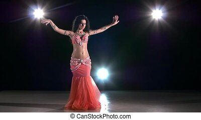 Beautiful exotic belly dancer woman dancing on black, back light, slow motion