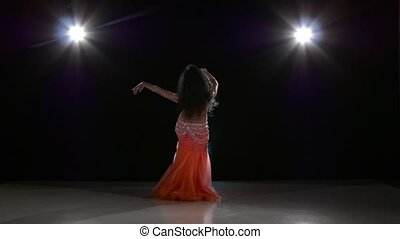 Beautiful exotic belly dancer young attractive woman dancing, on black, back light, slow motion