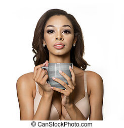 Beautiful exotic young woman holding hot drink in mug