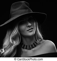 Beautiful expravagant makeup woman posing in fashion blue hat and gold necklace on dark black background. Black and white portrait