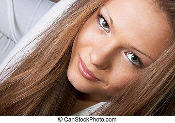 gaze of pretty long-haired girl in white. facial closeup.