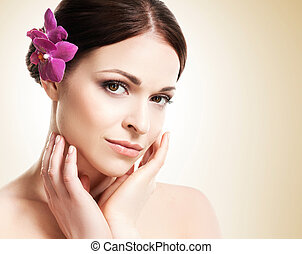 Beautiful face of a young and healthy girl with an orchid flower in her hair over yellow background