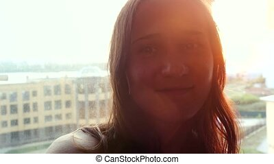 Beautiful face of young brunette woman in rays of the sun during sunset at window.