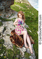 Beautiful fair-haired girl sits on plaid plaid at the cliff...