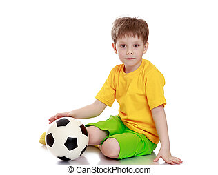 Beautiful fair-haired little boy in a yellow shirt and green shorts