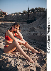 Beautiful fair-haired young girl in a red bathing suit on the beach