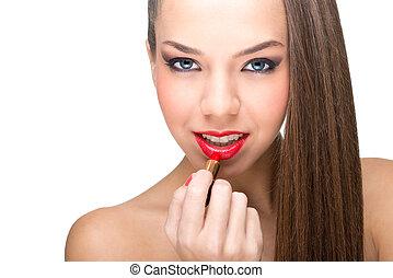 Beautiful fair skinned woman using a red lipstick