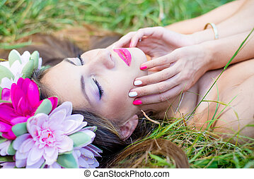 beautiful fairy: filtered image of brunette young pretty woman in lotus flower crown and pink makeup lying gracefully on green grass outdoors copy space background