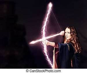 Beautiful fairy woman archer with a magic bow at night on...