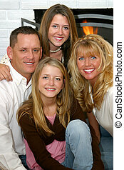 A beautiful family, father, mother and two daughters, smiling in front of their fireplace.