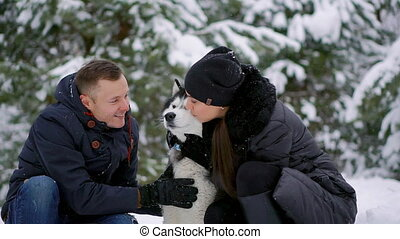 Beautiful family, a man and a girl in winter forest with...