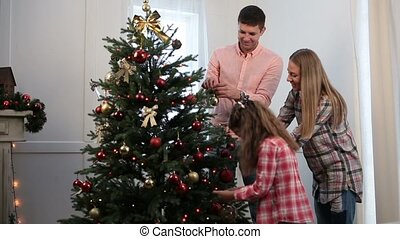 Beautiful family decorating Christmas tree