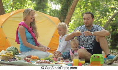Beautiful family eats on the nature having a picnic in the forest