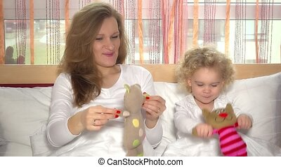 Beautiful family girls mom and toddler daughter playing with toy cats in bedroom
