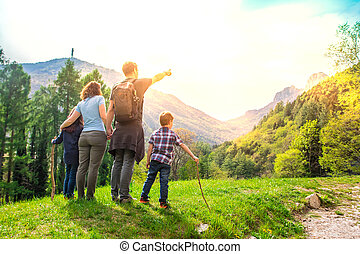 beautiful family is looking the landscape during a trekking