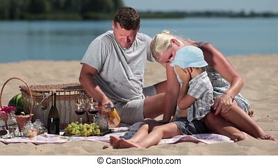 Beautiful family picnicking on the beach