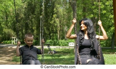 Beautiful family ride on a swing on a sunny day in the park
