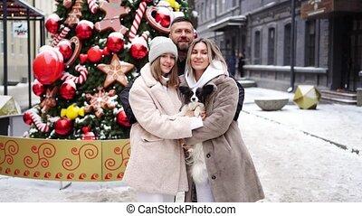 beautiful family with dog Papillon near Christmas tree on street.