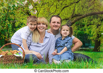 Beautiful family with kids having picnic outdoors