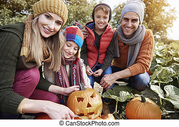 Beautiful family working on Halloween pumpkins