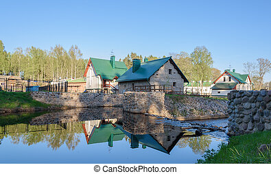 beautiful farm reflected in the river on background of blue sky