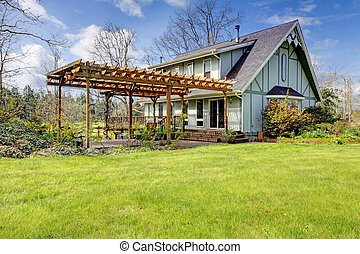 Beautiful farmhouse with attached pergola. Early spring - ...
