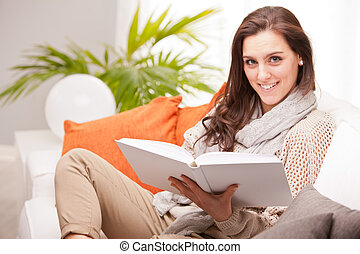 beautiful fascinating woman reading a book in her living room on a white sofa