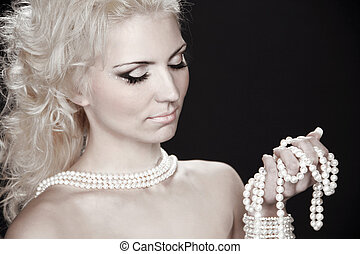 Beautiful fashion blonde woman with pearls, studio salon