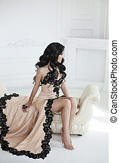 Beautiful fashion brunette woman in elegant dress with long wavy hair style sitting