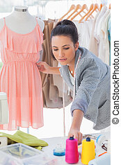 Beautiful fashion designer adjusting dress on a mannequin
