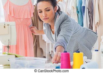 Beautiful fashion designer fixing dress