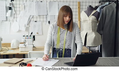 Beautiful fashion designer is drawing clothing sketches for...