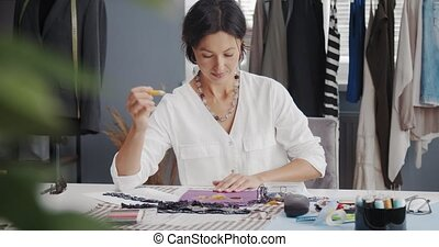 Beautiful fashion designer in white shirt sitting at table with sewing tools and sketching. Dark-haired woman making design of new trendy clothes.