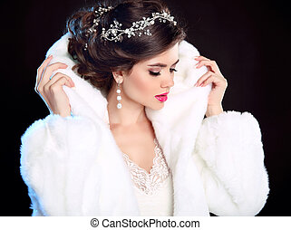 Beautiful Fashion Girl in White Mink Fur Coat. Jewellery. Winter portrait. Beauty woman model with elegant hairstyle and makeup posing isolated on dark studio background.